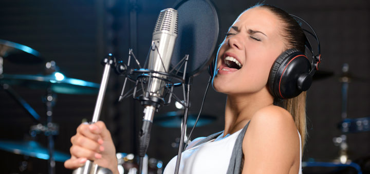 Portrait of young woman recording a song in a professional studio
